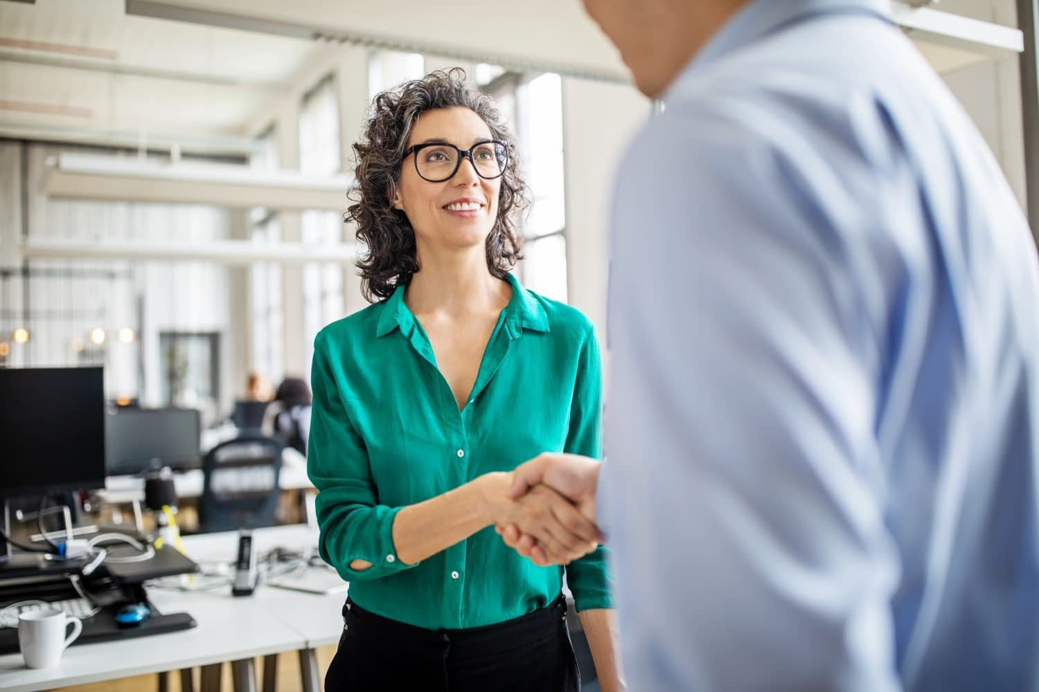 Mature woman shaking hands with male colleague. Mid adult business woman shaking hands with businessman in office.